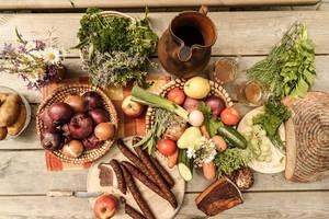 Ein Blick von oben auf einen Holztisch mit frischen, saisonalen und regionalen Wachauer Produkten vom Bauer & Wirt Langthaler (Gemüse, Kräuter, Wurstwaren, frisches Brot und geräucherte Spezialitäten)