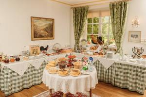 Das Bild zeigt das eindrucksvolle Genießerfrühstück im Hotel Garni Donauhof in Weißenkirchen. Im Vordergrund befindet sich ein runder Tisch  mit verschiedenen Müslisorten, eine Etagere mit frischen Früchten und auf den Seiten ladet das überbordene Buffet mit allerlei Wachauer Köstlichkeiten ein, das Frühstück in vollen Zügen zu genießen.