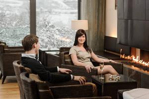 Entspannen und genießen im Cuvee Club des Steigenberger Hotel and Spa in Krems an einem kalten Wintertag. Ein junges Paar in schicker Kleidung genießt ein Glas Sekt vor dem offenen Kamin. Die großen Glasfenster geben die Blicke auf schneebeckte Bäume frei.